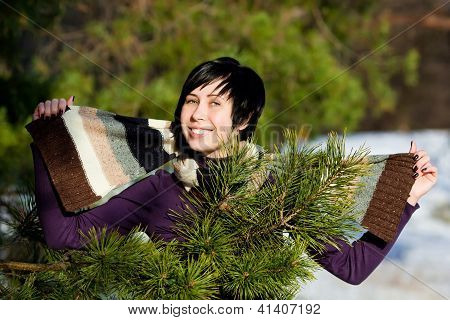 Beautiful young woman smiling in winter forest