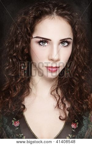 Portrait of young beautiful woman with curly hair and fancy make-up on vintage grainy damaged background