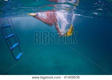 Underwater shoot of a person jumping in tropical sea with yellow fins