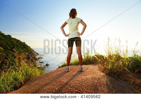 Young slim lady worn training clothes standing on top of a hill and enjoying sunset