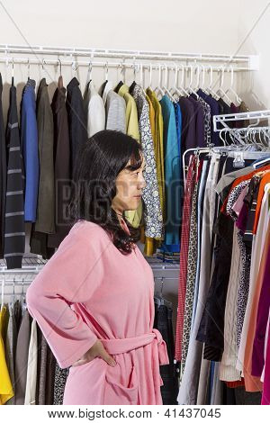 Mature Woman Looking At Clothing While In The Her Walk-in Closet