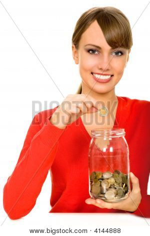 Woman Putting Coin In Jar