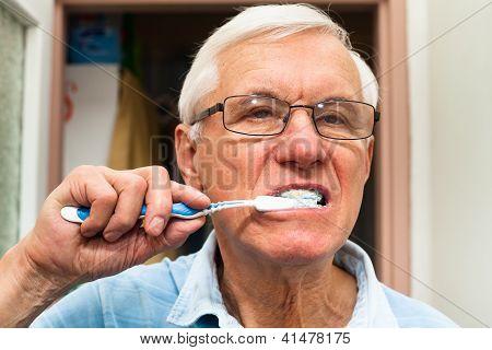 Homem sênior escovar seus dentes