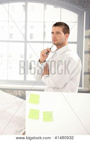 Bonito jovem engenheiro trabalhando em escritório brilhante, fazendo planos.