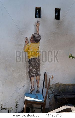 PENANG, MALAYSIA-DEC.9: Street Mural entitled 'Reaching Up'  painted by Ernest Zacharevic in Penang on Dec.9, 2012. It was painted in conjunction with the 2012 George Town Festival.