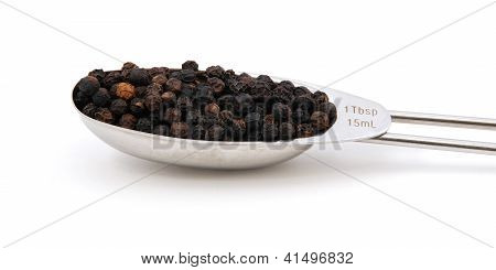 Black Peppercorns Measured In A Metal Tablespoon