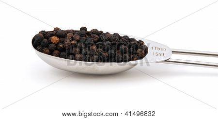 Black Peppercorns Measured In A Metal Tablespoon