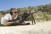 picture of shooting-range  - Side view of a man in shooting position on shooting range - JPG