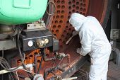 stock photo of ppe  - An engineer wearing his ppe and working on an industrial steam boiler having its clean and refit - JPG