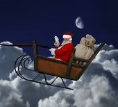 stock photo of santa sleigh  - Santa in his sleigh flying throught a nighttime cloudscape - JPG