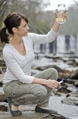 stock photo of groundwater  - Female researcher testing the water quality in a river - JPG