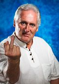 foto of obscene  - An angry grumpy mature man giving the rude middle finger and looking at camera - JPG