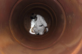 foto of ppe  - An engineer wearing  correct ppe for an industrial boiler clean inside the furnance - JPG