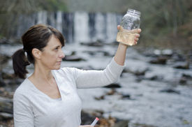 pic of groundwater  - Female researcher checking the water quality from a river - JPG