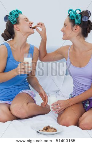Pretty friends sitting in bed having milks and cookies laughing at sleepover