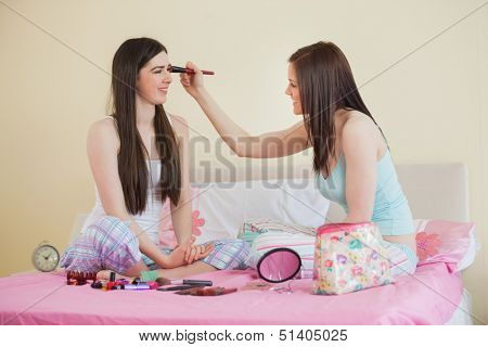Smiling girl giving her friend a makeover at sleepover in bedroom at home