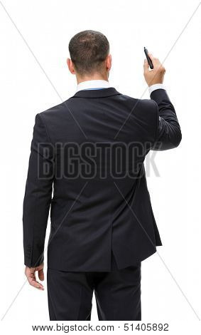 Half-length backview of businessman writing with marker on imaginary screen, isolated on white. Concept of leadership and success