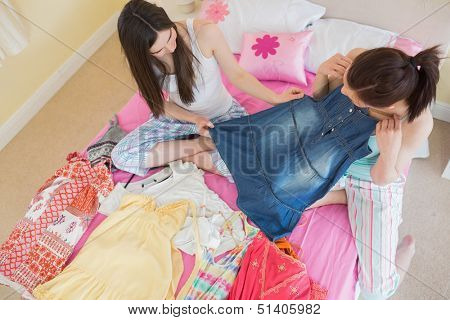 Cute girls looking at a denim dress at a sleepover at home in bedroom