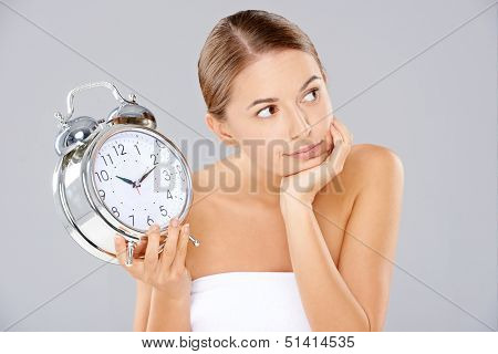 Attractive bored young woman wearing a white towel sitting with an oversized classic retro alarm clock with bells in her hand looking off to the right of the frame with a serious expression