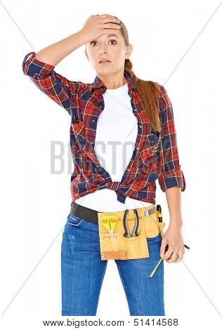 DIY handy woman with a dazed expression standing with her hand raised to her forehead in a knotted plaid shirt with a tool belt around her waist  isolated on white