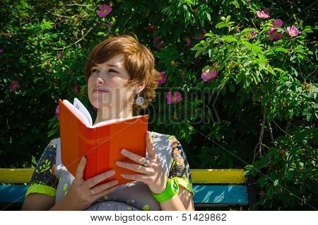 Pregnant Woman Reading Notebook On The Bench And Smiling