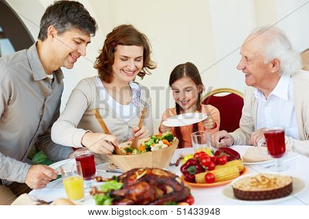 Portrait of happy family sitting at festive table while having Thanksgiving dinner