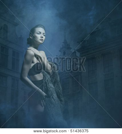 Young attractive woman in lingerie over the old town background
