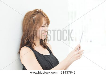 Beautiful asian woman using a tablet computer in the room