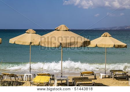 Three Orange, Old  Parasols And Sunlounger With Blue Ocean In Background