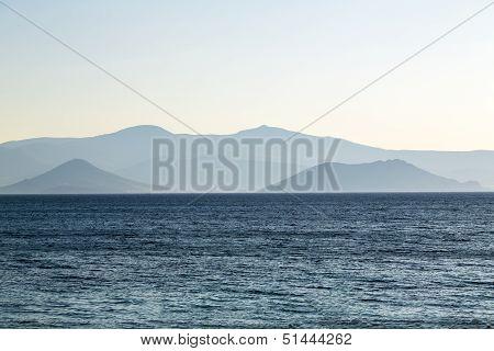 Pale Mountain Chain In A Blue Ocean