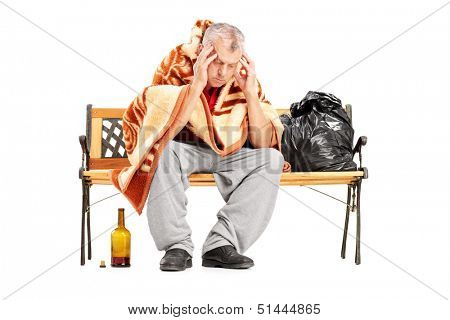 Disappointed homeless mature man sitting on a wooden bench isolated on white background