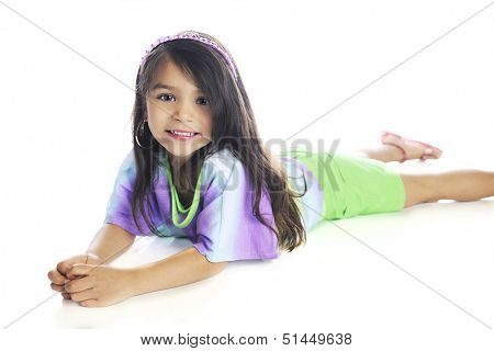 A beautiful elementary girl happily looking at the viewer as she lays on her belly in casual, summer clothes.  On a white background.