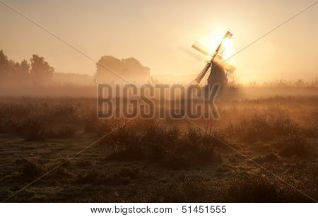 Sunshine Behind Windmill In Morning Fog
