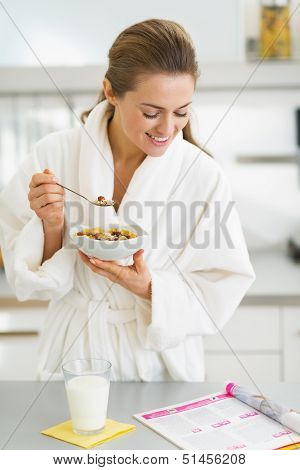 Happy Young Housewife In Bathrobe Having Healthy Breakfast And R