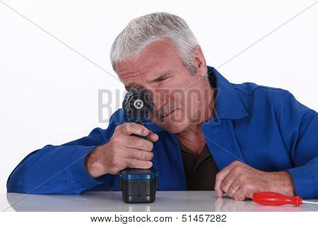 Grey haired handyman with cordless drill