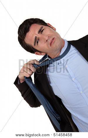 A businessman untying his tie.