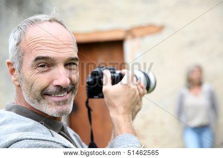 Senior photographer using digital camera