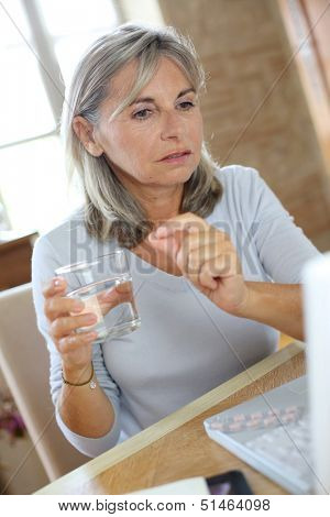 Senior woman reading medication instructions on internet