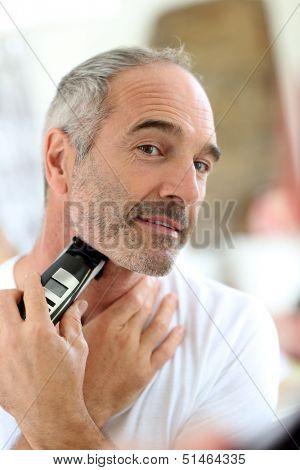 Senior man shaving beard with electric razor