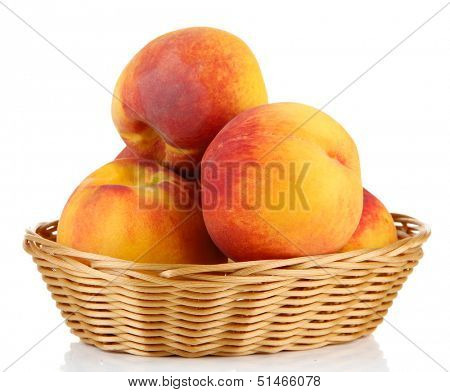 Ripe sweet peaches in wicker basket, isolated on white