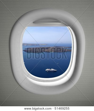 Airplanes window seat view with sea scape and islands