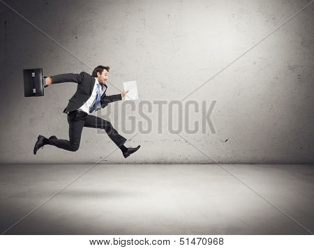businessman running with some documents in his hand