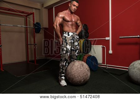 Muscular Man Resting After Picking Up A Stone