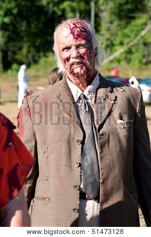 Elderly Male Zombie Prepares To Menace Runners In 5K Race
