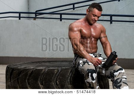 Healthy Man Resting And Drinking Water After Exercising In Gym