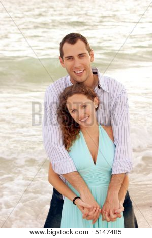 Smiling Couple Holding Each Other Looking At Viewer