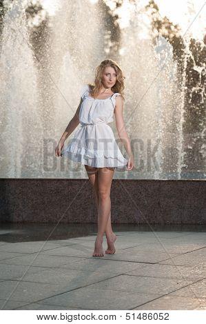 Beautiful blonde women near the fountain in a ballet position