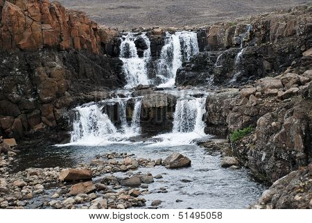 Landscape With Rocks And A Waterfall.