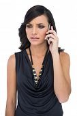 picture of frown  - Frowning elegant brown haired model talking on the phone on white background - JPG