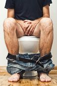 stock photo of defecate  - Man sitting on toilet with his pants down - JPG